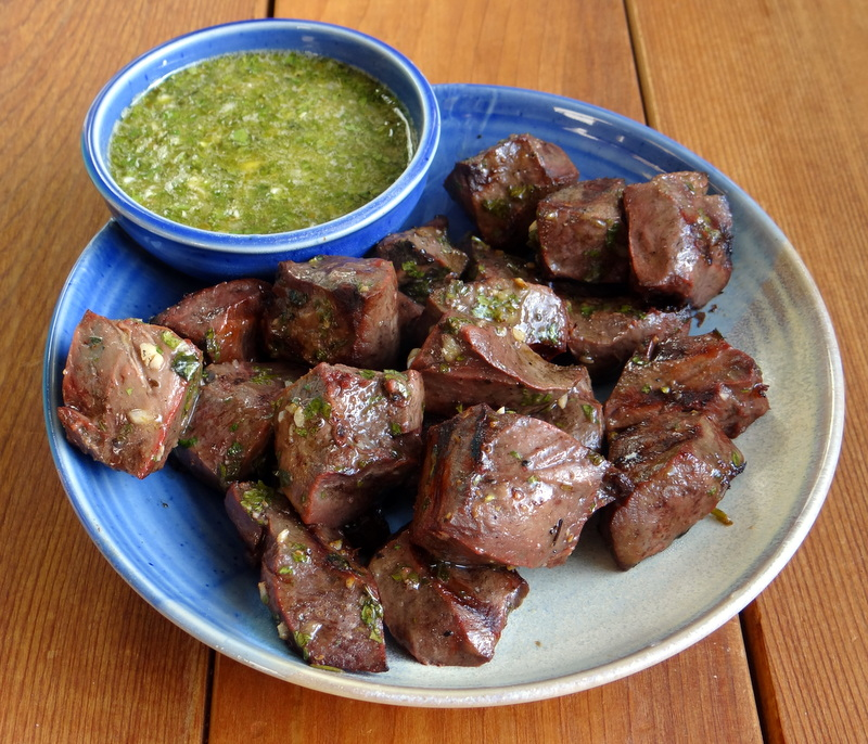 photo of beef heart cubes on a plate, with chimichurri dipping sauce