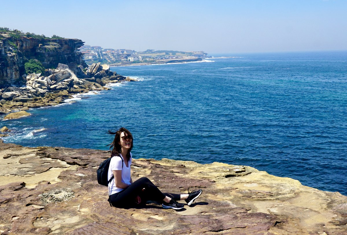 Evelyn sitting a cliff overlooking the ocean, laughing with the wind blowing through her hair