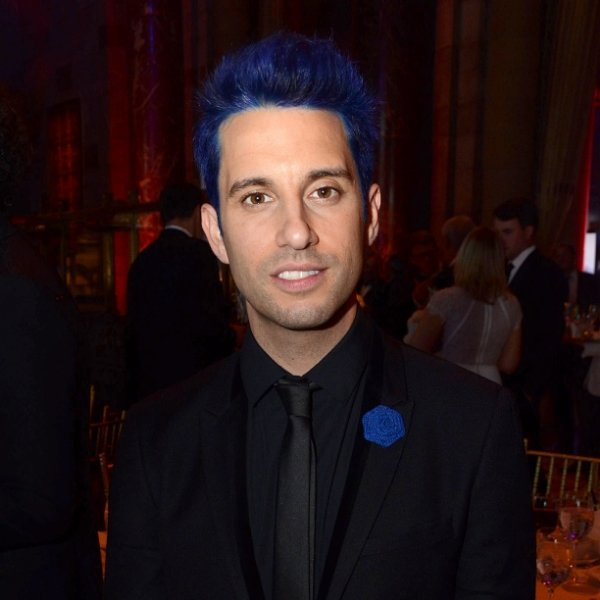 Chad King dressed in a black suit, with hair dyed blue.