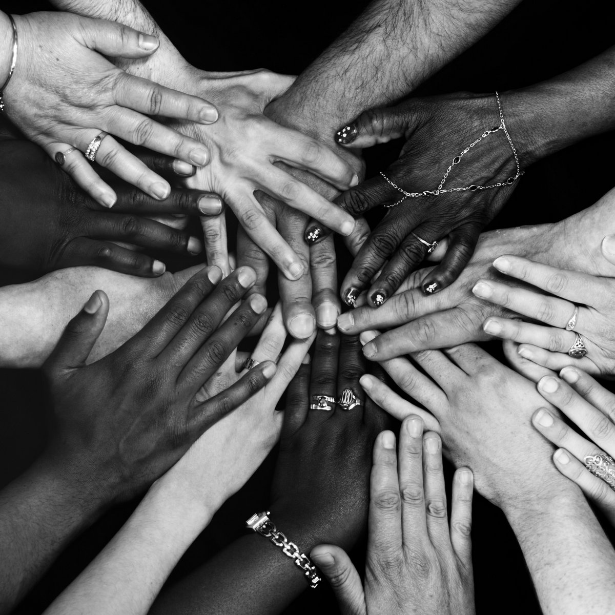 Hands of many different colors and ethnicities laid on top of each other representing unity and connection
